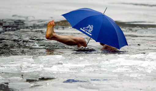 A member of the 'Seehunde Berlin' winter and ice swimming club, swims with an umbrella in the frozen Oranke Lake in Berlin, Friday, Dec. 25, 2009. It is an annual event that club members meet for a Christmas swim at the lake.