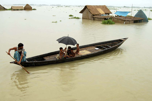 Flood crisis: A villager rows a boat past huts submerged in floodwaters in Bhakatpur, in the northern Indian state of Assam.