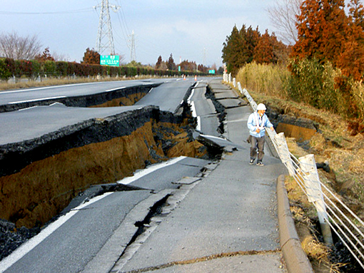 In this photo released by Nexco East Japan, a worker inspects a caved-in section of the Joban Motorway near Mito, Ibaraki.