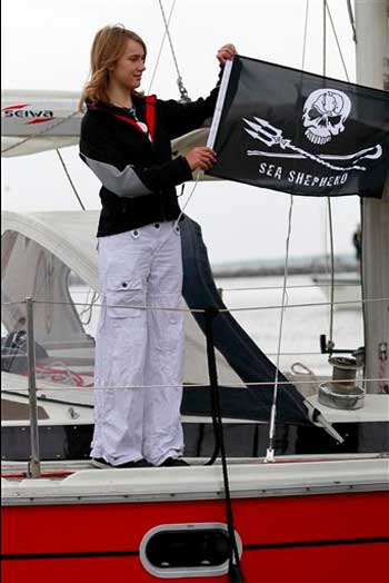 14-year-old Laura Dekker hoists a flag of the Sea Shepherd Conservation Society at her 38-foot (11.5-meter) yacht Guppy setting off on a sail around the world by herself