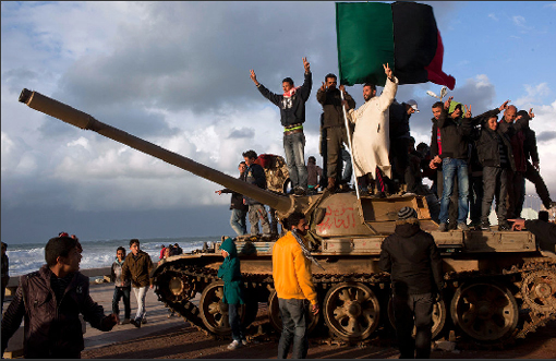 Eastern Libyans celebrate atop a surrendered military tank in the town square of Benghazi on Thursday