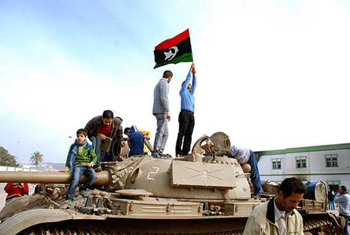 Protesters stand on a tank holding a pre-Qaddafi era national flag inside a security forces compound in Benghazi, Libya, on Feb. 21