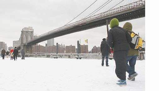 Brooklyn Bridge provides the backdrop as tourists brave the snow in New York