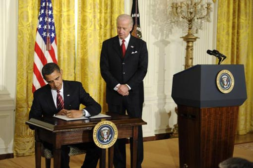 President Barack Obama (L), joined by Vice President Joe Biden, signs a set of executive orders that will strengthen the working rights of federal contract workers during a ceremony where he announced Vice President Joe Biden as the head of the newly created Middle Class Working Families Taskforce in Washington on January 30, 2009
