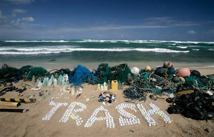 The word 'trash' is spelled out using golf balls retrieved by Greenpeace. Some of the other debris recovered during a cruise off Hawaii is displayed as well on Honolulu's Kahuku Beach.