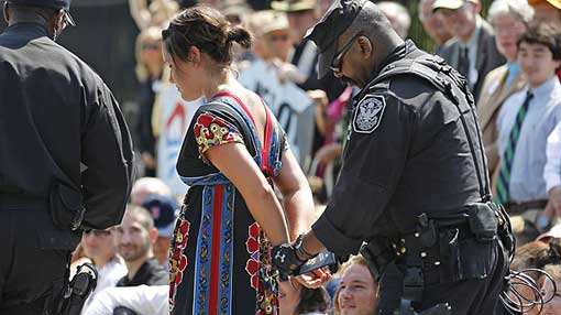 US Park Police officer handcuffs and arrests a protestor over a proposed pipeline to bring tar sands oil to the US from Canada