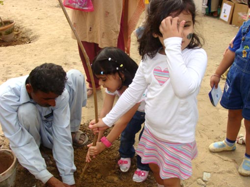 little Pakistani girl helps plant a tree