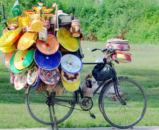 A Pakistani vendor takes a nap beside his bicycle carrying colour handicrafts at a roadside in Islamabad.