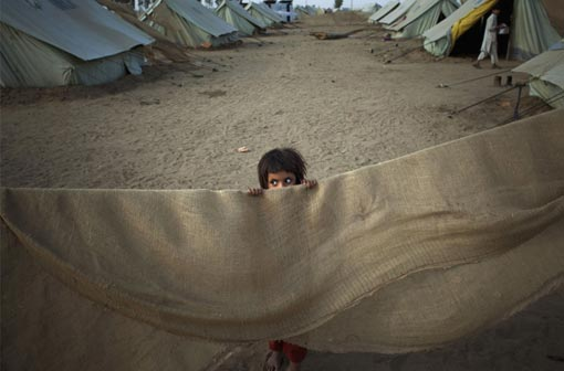 a Pakistani girl peers over part of a makeshift tent in Chota Lahore Refugee Camp in Swabi, Pakistan on Wednesday, May 20, 2009