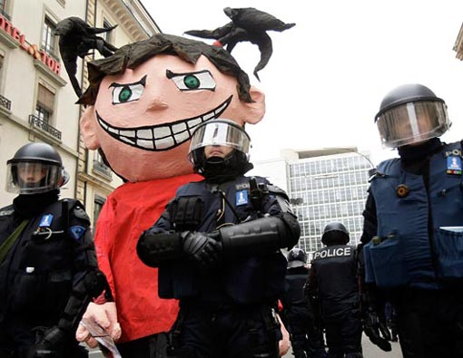 riot police officers stand around a giant anti-World Economic Forum mascot on wheels after confiscating the figure during a protest against the Davos forum in Geneva