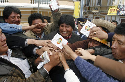 President Evo Morales hands out copies of the new Constitution during a demonstration outside the governmental palace and after the congress passed the law to call a referendum on it, on October 21, 2008 in La Paz