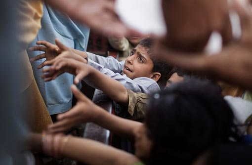 internally displaced children scramble to get a piece of ice being handed out by aid workers at the Chota Lahore relief camp on May 20, 2009 in Swabi, Pakistan