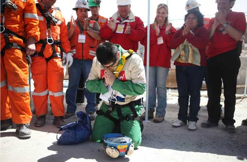 rescued Chilean miner prays after being rescued from collapsed mine