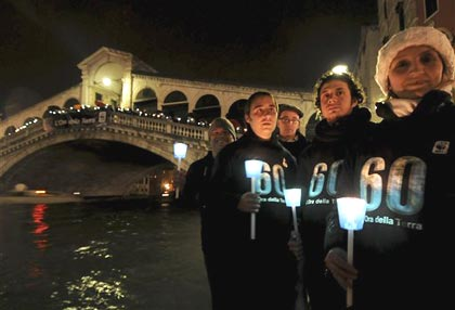 WWF (World Wildlife Fund) activists stand with candles as The Rialto Bridge lights are lit off, in Venice, Italy, Saturday, March 28, 2009