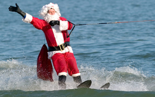 A man dressed as Santa Claus water skis on the Potomac River at the National Harbor in Prince George's County, Maryland, near Washington, DC, on December 24, 2009. Joined by flying elves, Frosty the Snowman in a dinghy and kneeboarding reindeer, Santa celebrates his 24th anniversary of water-skiing in the Washington area on Christmas Eve.