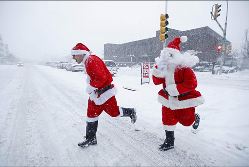 People dressed as Santa Claus cross a street on their way to a bar during a snow storm in Philadelphia, Saturday, Dec. 19, 2009.