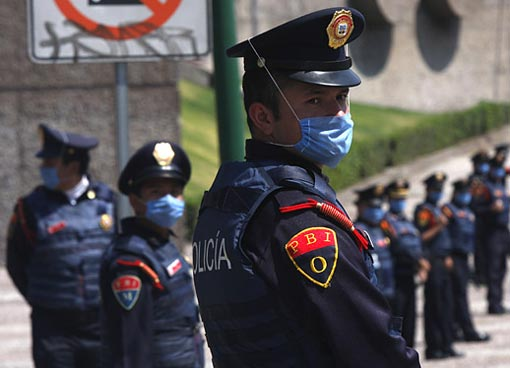 Riot police stand in front of Mexico's National Autonomous University soccer stadium. Despite being a sell-out, the famous volcanic-rock bleachers were empty due to the crisis