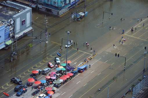 people wading through floodwaters on the main road of the ancient Thai capital of Ayutthaya, north of Bangkok, on October 11