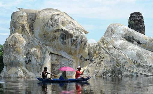 Villagers paddle past an inundated leaning Buddha statue in Ayutthaya Province on October 10.