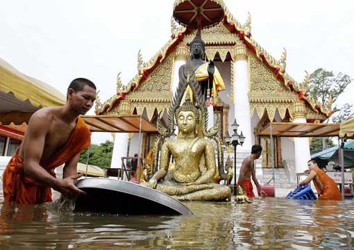 Buddhist monks collect their belongings at a flooded temple in the ancient city of Ayutthaya, Thailand, on October 7.