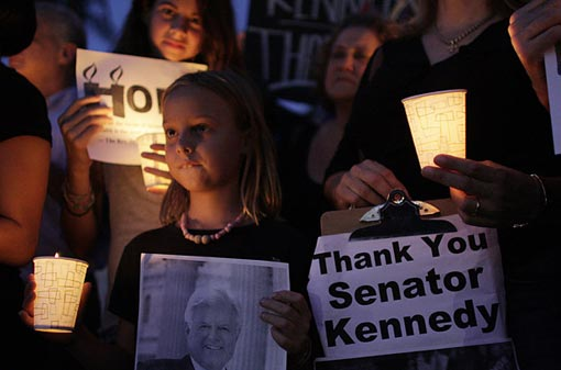 Olivia Kelly, 8, left, and Dion Osborne, 11, rear, hold signs in memory of Sen. Kennedy at a candle light vigil in Miami.