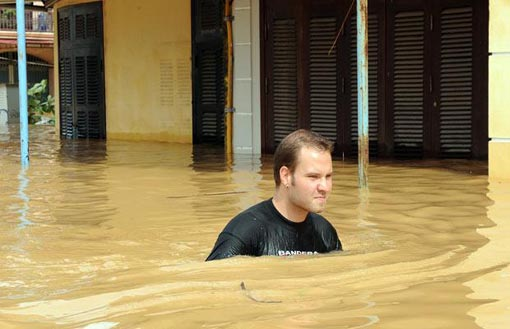 a foreign tourist wades on a flooded street in the town of Hoi An