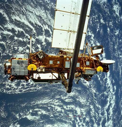 the Upper Atmosphere Research Satellite hangs in the grasp of the Remote Manipulator System during deployment from Space Shuttle Discovery, September 1991
