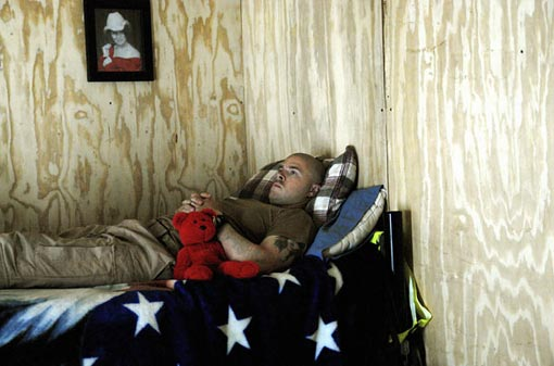 A helicopter medic waits in his ready hut in Baghdad for a call to action. His girlfriend had sent him the teddy bear for good luck. He had another one hanging next to his carbine on the chopper.