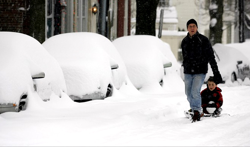 Pedestrians walk down a snow-covered road in Old Town, Alexandria, Va.