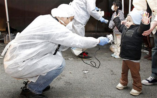 officials in protective gear check for signs of radiation on children who are from the evacuation area near the Fukushima nuclear plant