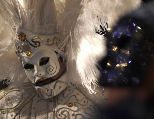 Masked revellers pose in Saint Mark's Square during the Venetian Carnival