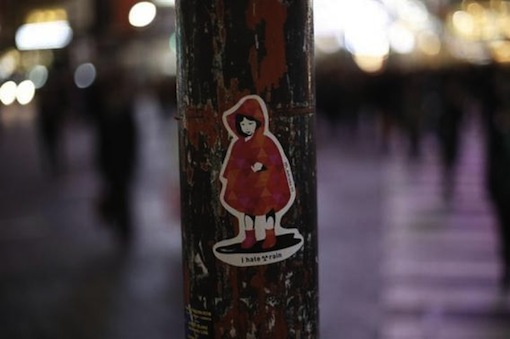 Little girl with a message 'No Nuclear Rain' on sticker art seen on a traffic light in Tokyo.