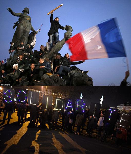 demonstrators wave pencils and flags at Place de la Nation and sign spelling out the word Solidarity
