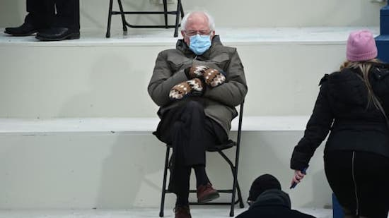 Bernie Sanders in fashion on Inauguration Day: mask on, mittens oversized, sitting on a folding chair, distancing from all the rest.  Photo goes viral